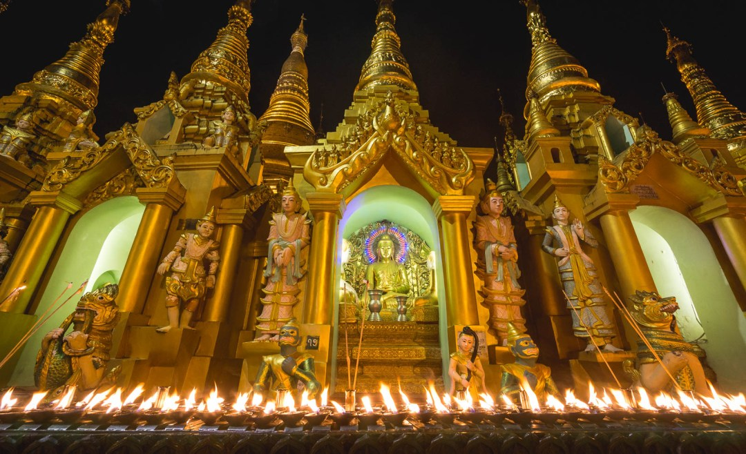 Candles lit in front of Buddha at pagoda