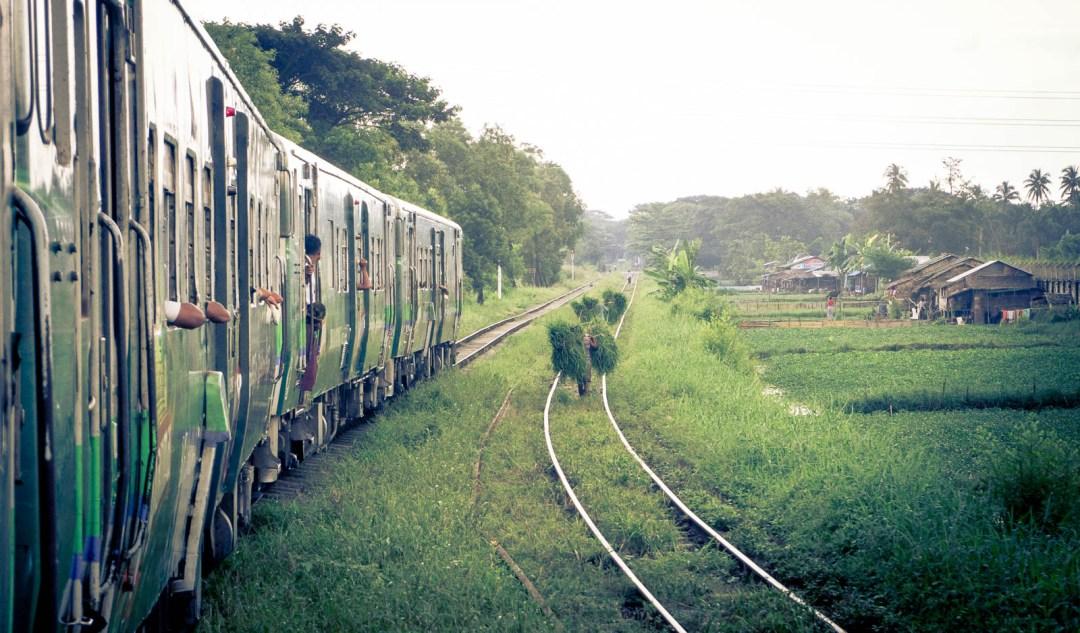 Villagers walking along railroad track beside train