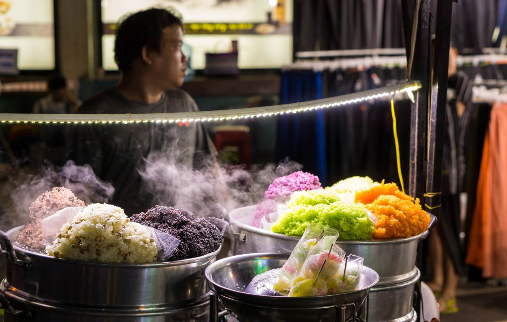 Colourful rice cooking on street vendors stall