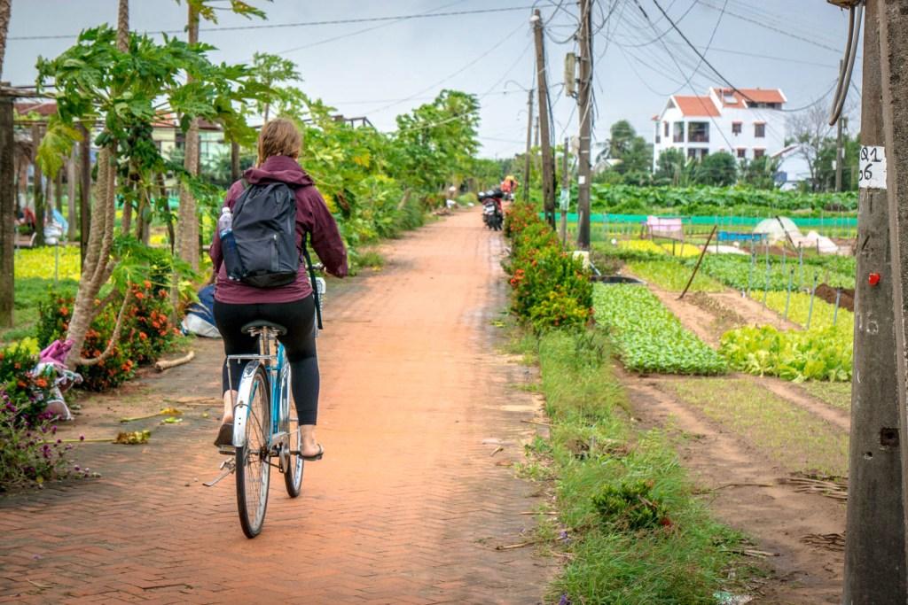 Hilary riding a bike through vegetable village
