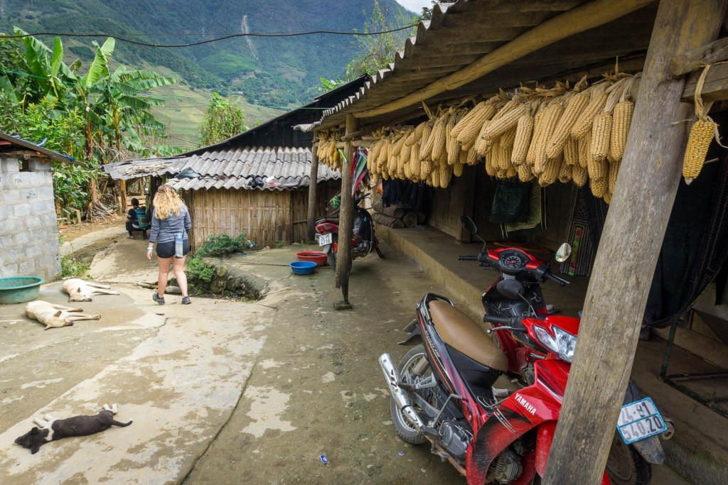 HIlary walking through small village in Sapa with corn hanging