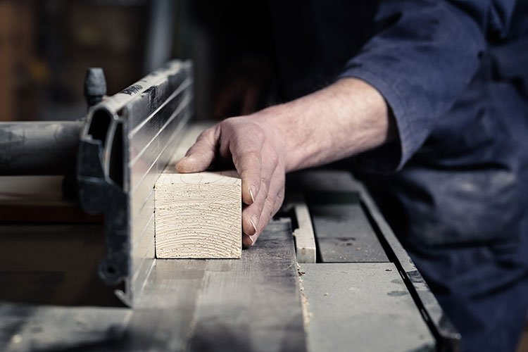 woodworker cutting wood on a tablesaw