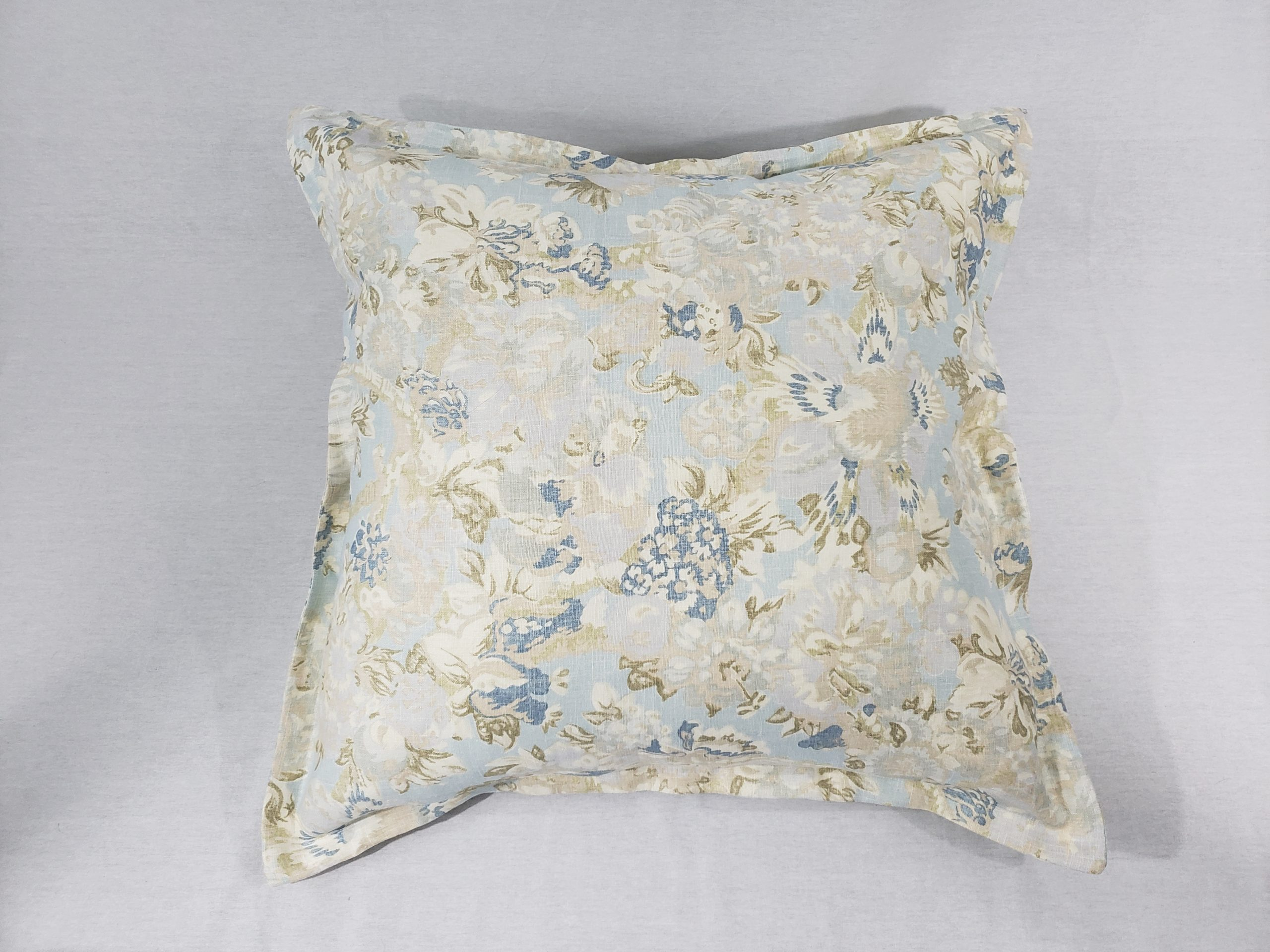 A baby blue floral cushion with flange