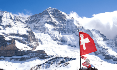Flag of Switzerland flying against a backdrop of a blue sky and mountains.