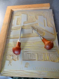 photo of printmaking lino and carving tools on wooden bench hook