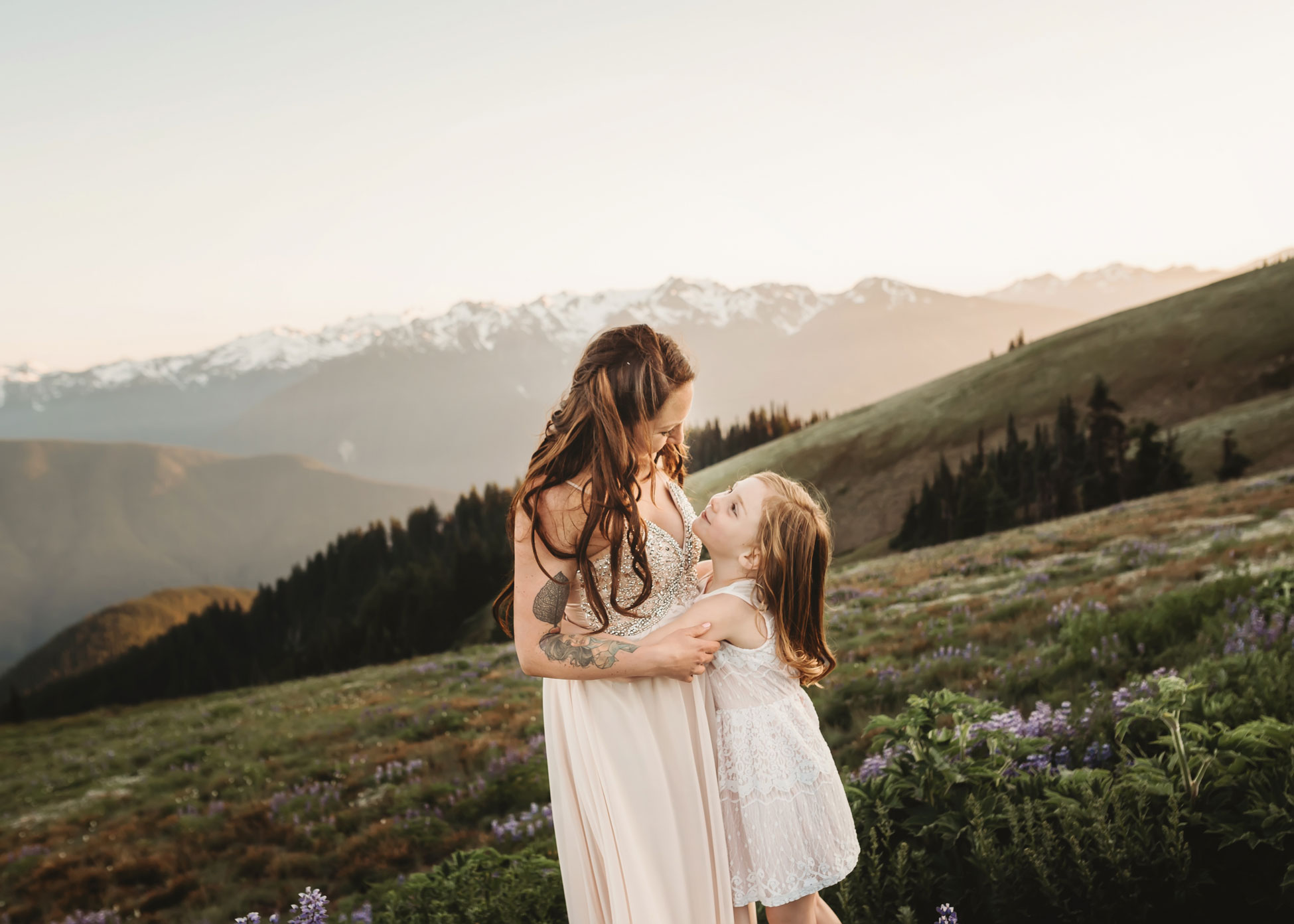 mother and daughter snuggling in the mountains