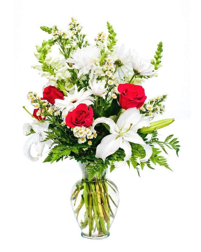 Mazzo di fiori per fare le condoglianze, caratterizzato da variètà tradizionali, le quali lillium, bocche di leone e rose rosse