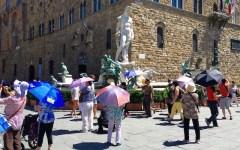 Caldo: 34 gradi a Firenze. Turisti con l'ombrello contro il sole a picco. Le temperature in Toscana