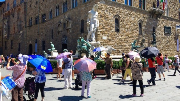 Turisti con l'ombrello oggi in piazza Signoria a Firenze alle 14