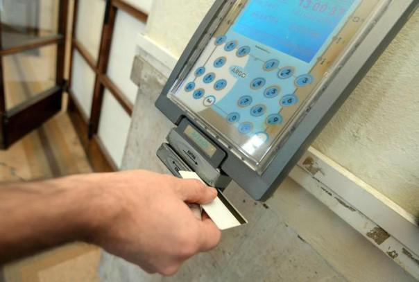Un impiegato statale timbra il cartellino all'uscita del lavoro in una foto di archivio. ANSA/FRANCO SILVI
