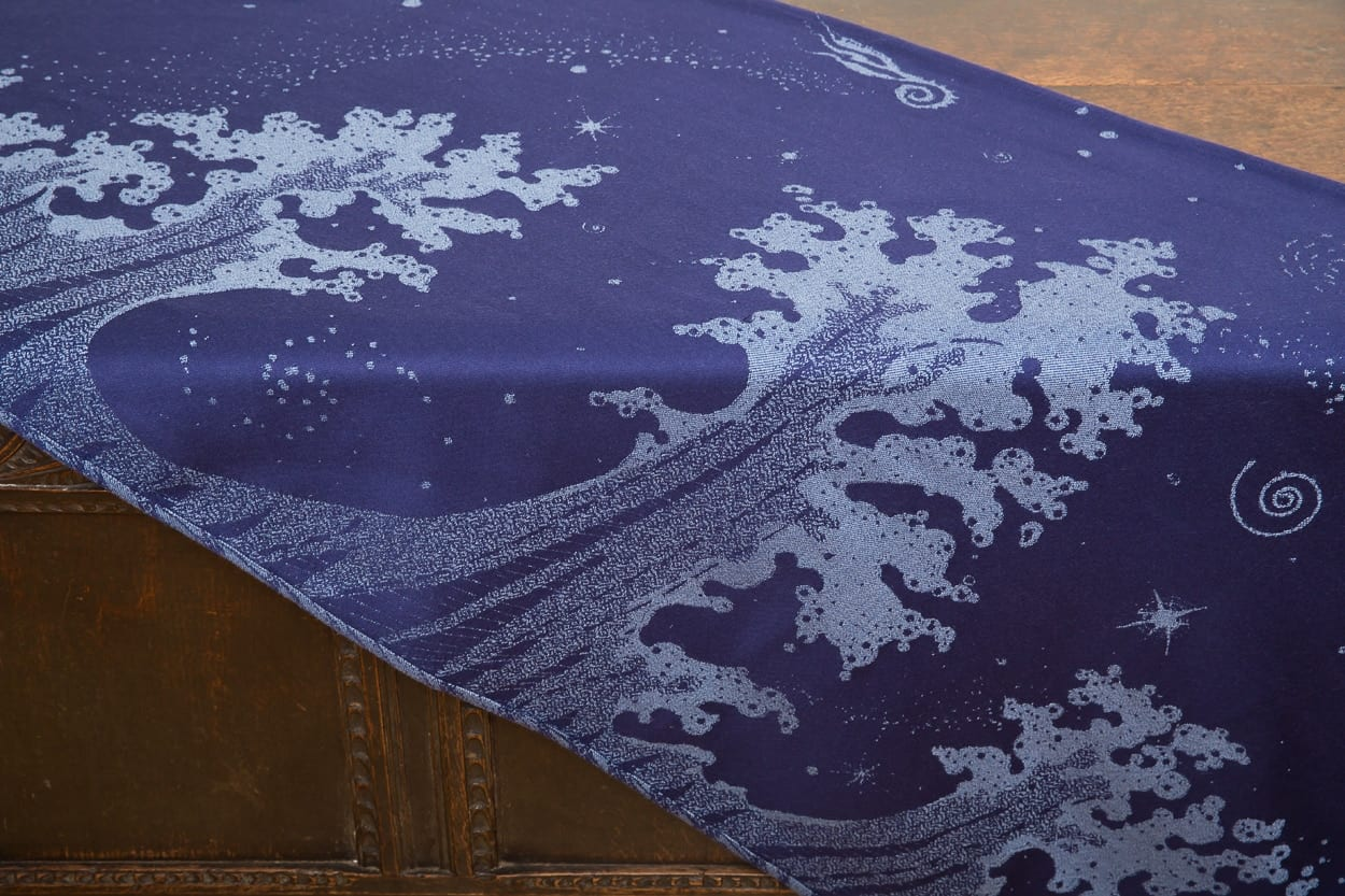 flat shot of a dark blue and grey woven wrap with a crashing wave design