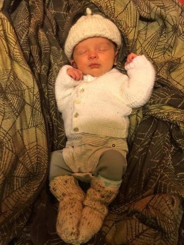 sleeping newborn lying on a woven wrap