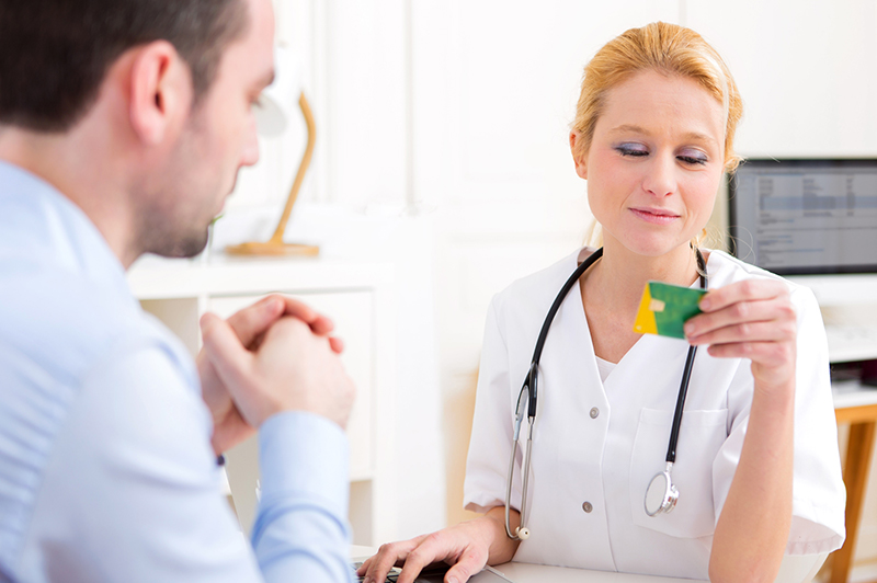 Female nurse checking a patient's credit card