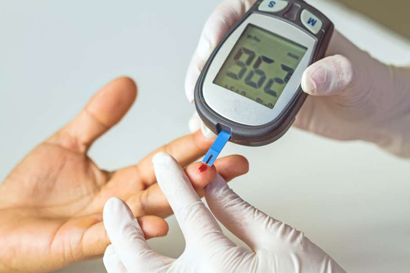 Doctor taking blood sugar test for a diabetic patient