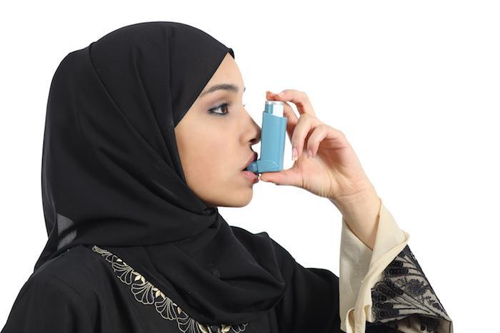 Young woman using an inhaler for her asthma