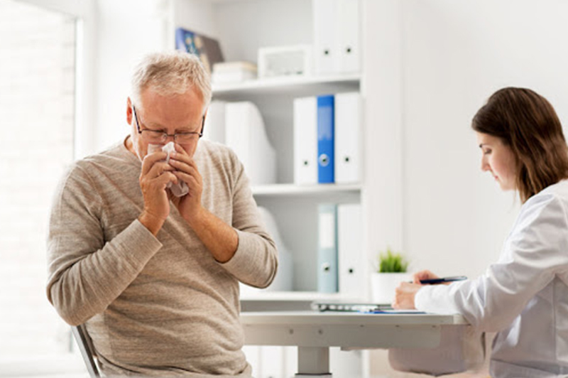Senior citizen with a cold visiting a doctor for a sick visit