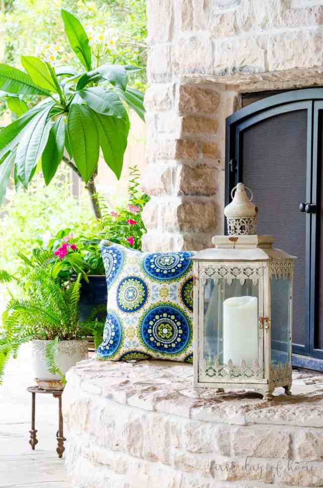 Lantern on fireplace hearth with Moroccan pillow and greenery in background