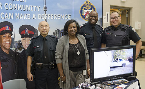 Constable James Wong, Employment Manager Annmarie Henry, Sergeant Chris Gordon, and Constable Joe Lee at a Toronto Police Service recruitment display.