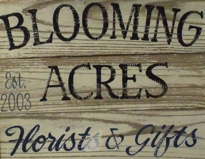 Photo of the wooden sign at the entrance to Blooming Acres in the First Street Community Center in Mount Vernon, Iowa