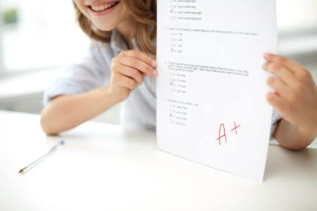 happy girl with test paper at school