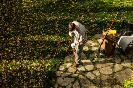 Man raking leaves on sunny autumn day in back yard high angle view