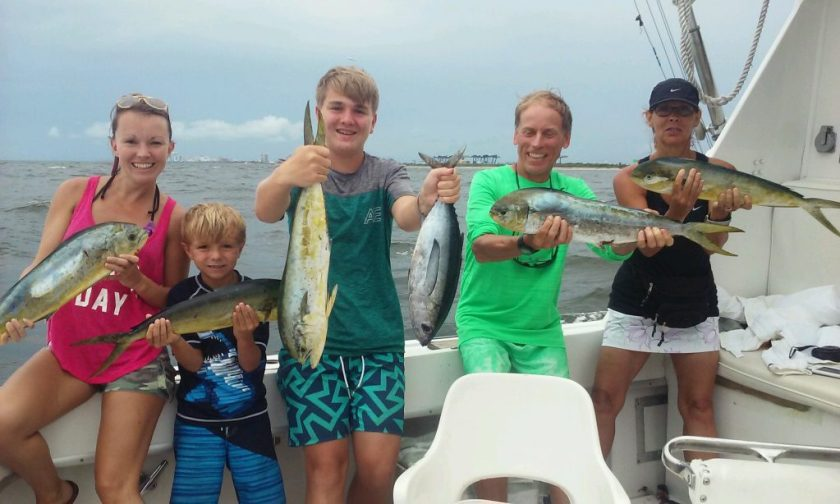 Family holding their fish up out at sea, bunch of dolphin and tunas.