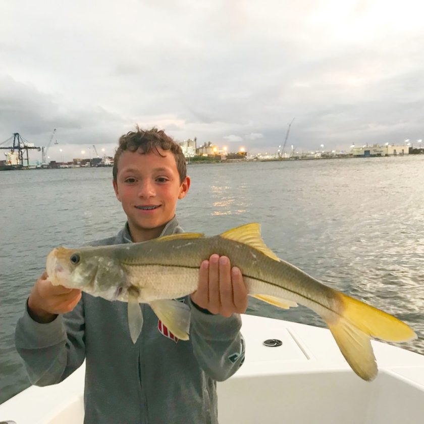 Adolescent boy holding a nice snook he just caught aboard the boat just around sunset on an inshore fishing charter with Port Everglades in the background.
