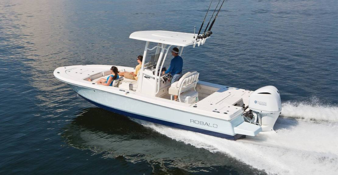 robalo boat in the water. two people are sitting in the bow and one person is steering the boat