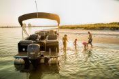 a family of four by a Premier Pontoon Escalade boat