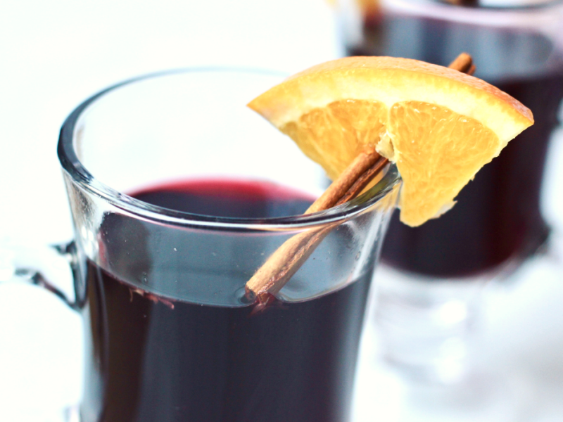 Glass of hot mulled wine in a mug with cinnamon stick and orange wedge. Perfect Christmas beverage! This festive hot mulled wine is easy, delicious, and healthy! The perfect drink on a cold winter day to warm you from the inside out.
