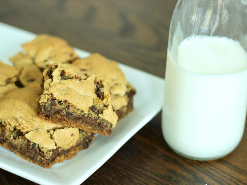 stack of decadent Nutella-stuffed chocolate chip cookie bars with milk