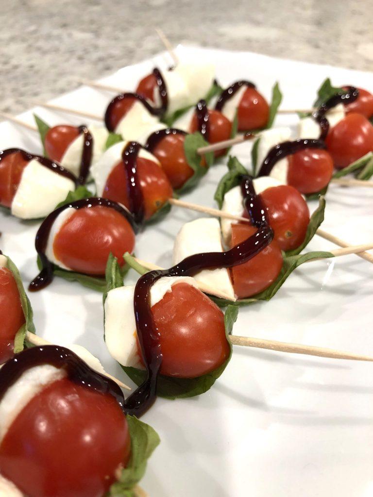tomato mozzarella caprese bites on a platter