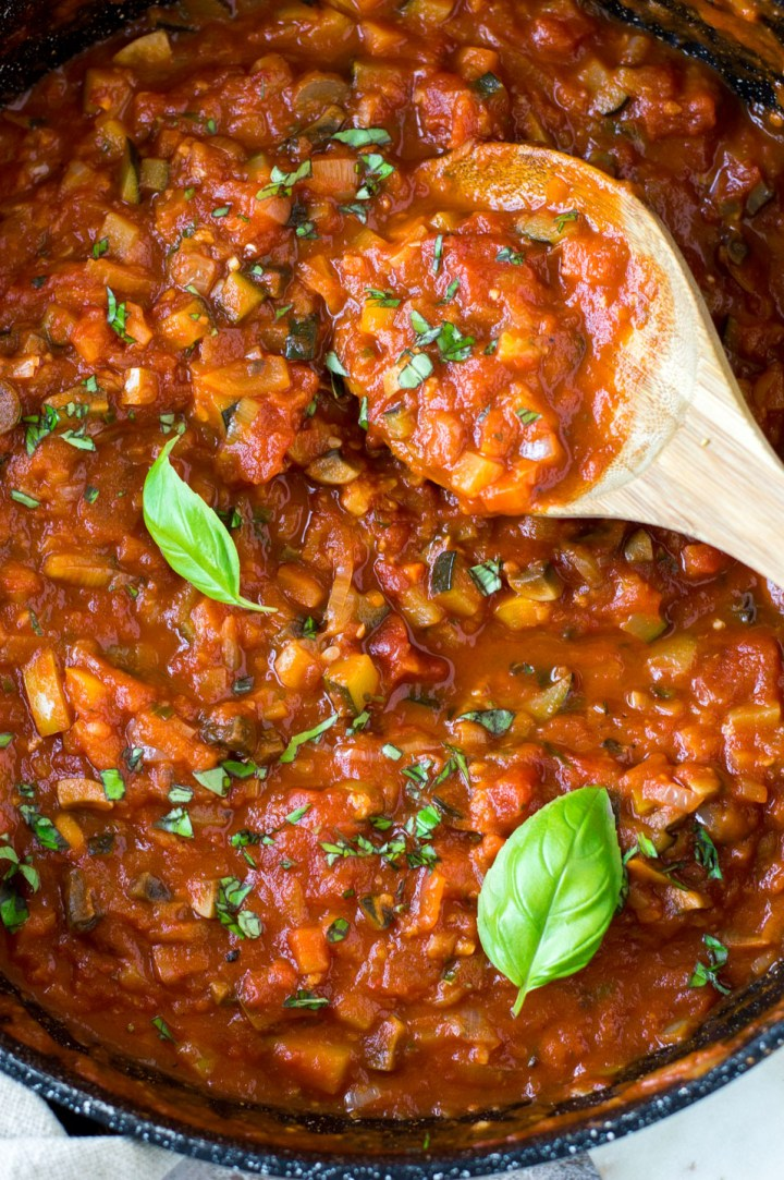 Top down view marinara sauce in a black saucepan with wooden spoon and basil leaves