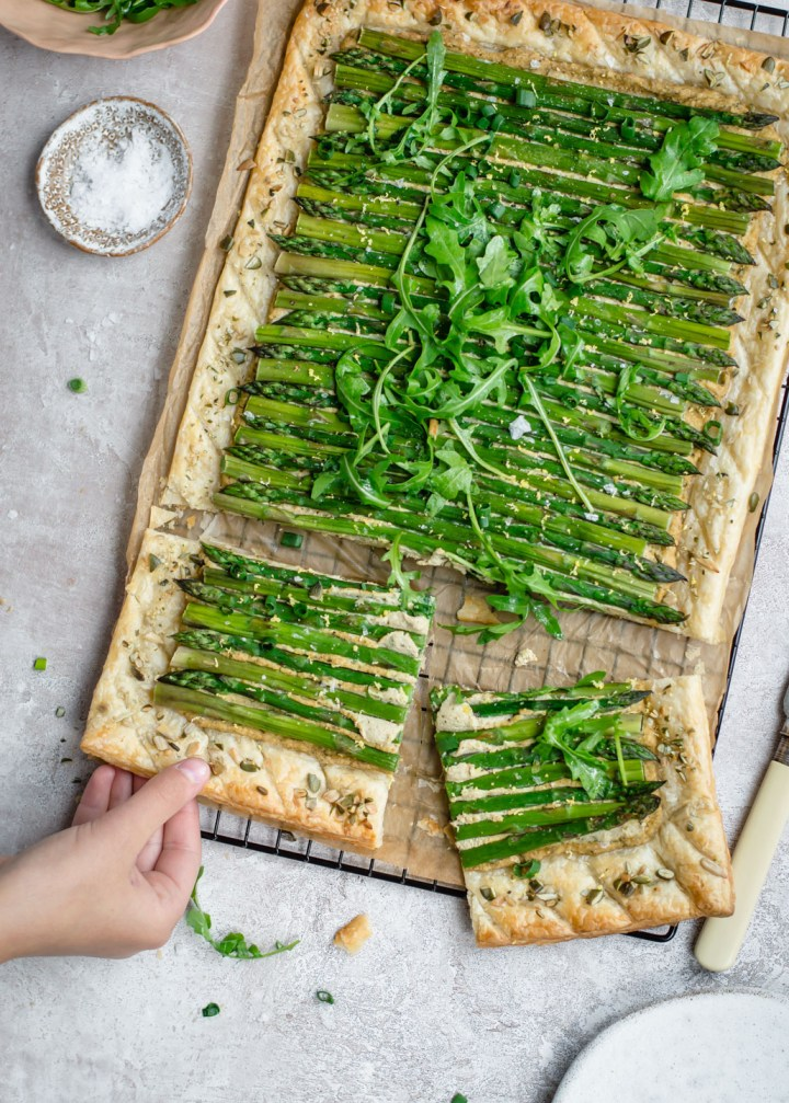 Top down view of asparagus tart with a hand reaching for the slice