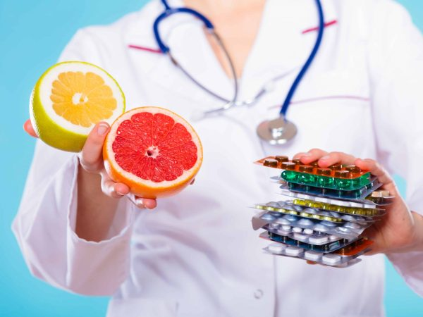 Health and balanced diet concept. Choice between two sources of vitamins – pills or fruits. Medical doctor offering chemical and natural vitamins, holding stack of drugs and grapefruits on blue.