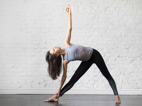Young woman practicing yoga, standing in Utthita Trikonasana exercise, extended triangle pose, working out, wearing sportswear, gray tank top, black pants, indoor full length, studio background