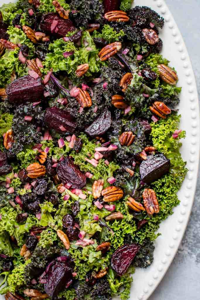 roasted beet salad with kale and pecans on white platter