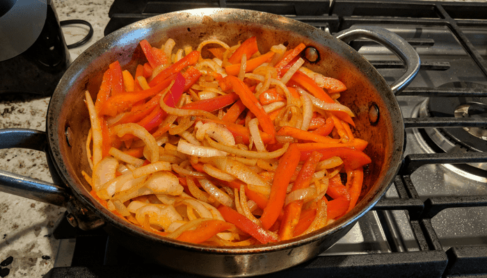onions and peppers in pan cooking