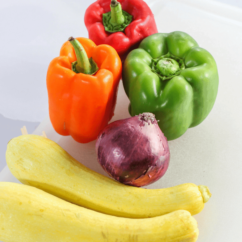 summer vegetables squash, green bell pepper, red bell pepper, red onion washed for veggie kabobs