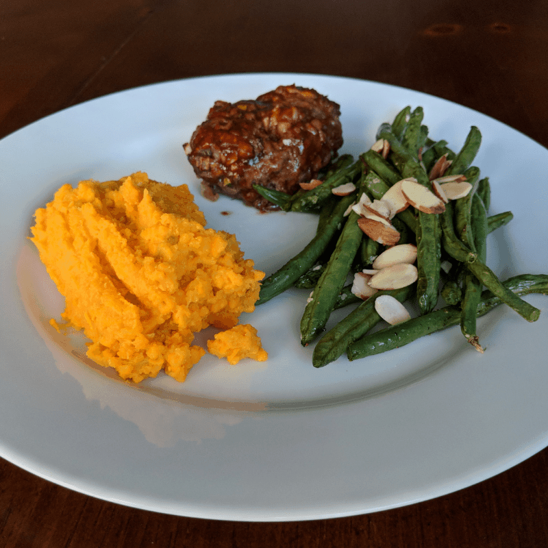 sweet potatoes, green beans with sliced almonds, mini meatloaf on white plate for high carb day dinner