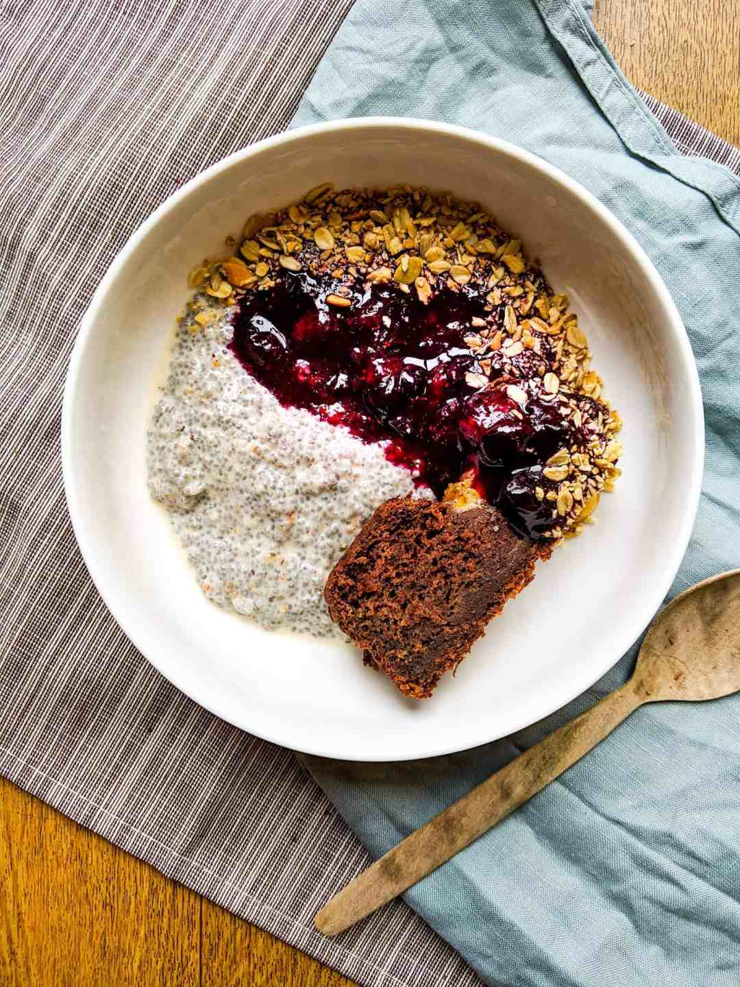 chia seed pudding with stewed berries in a white bowl with a wooden spoon beside it