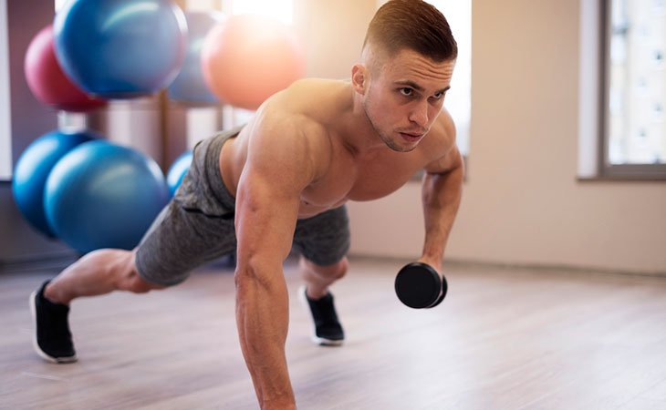 Man Using Dumbbell Chest Roll Pushup