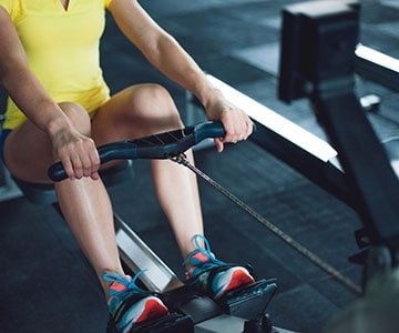 Woman Using Rowing Machine At Home