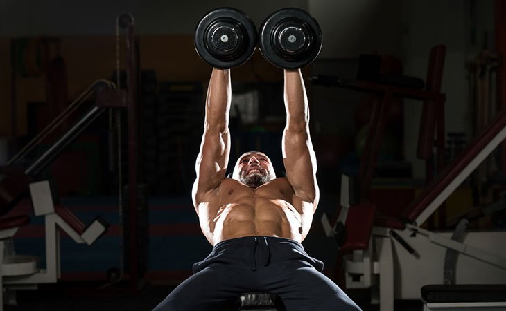 Man Using Dumbbell In Low Incline Chest Press