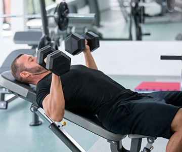 Man Working Out Using Dumbbells And Weight Bench