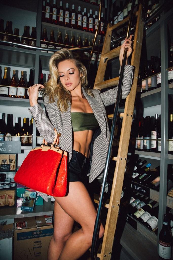 Savannah Lynx legs in a wine cellar red purse