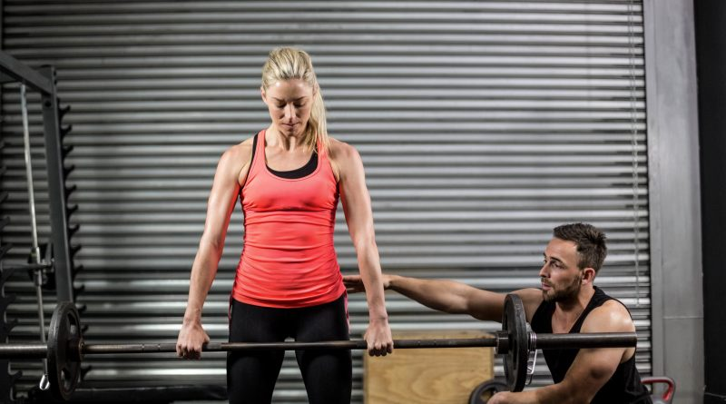 Pricing Personal Training Sessions: Featured Image. Personal Trainer Coaching Client on Dead lift.