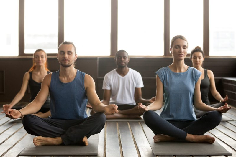 """Featured image of """"should you open a fitness studio""""?: The image is a group of young people meditating in a yoga studio."""