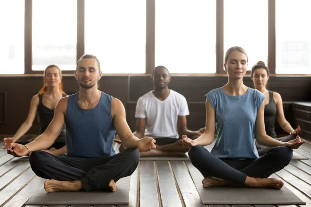 "Featured image of ""should you open a fitness studio""?: The image is a group of young people meditating in a yoga studio."