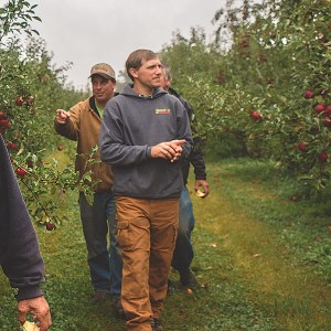 Farmers walking in orchard - Five Acre Farms